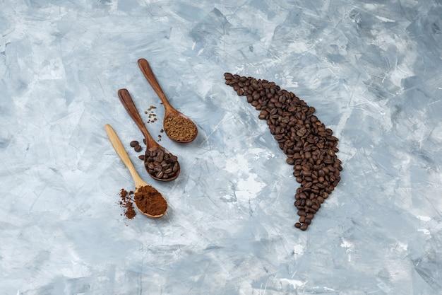 Hoge hoek bekijken koffiebonen met koffiebonen, instant koffie, koffiemeel in houten lepels op lichtblauwe marmeren achtergrond. horizontaal