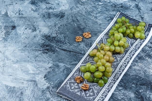 Hoge hoek bekijken verse druiven met walnoten op grunge en keuken handdoek achtergrond. horizontaal