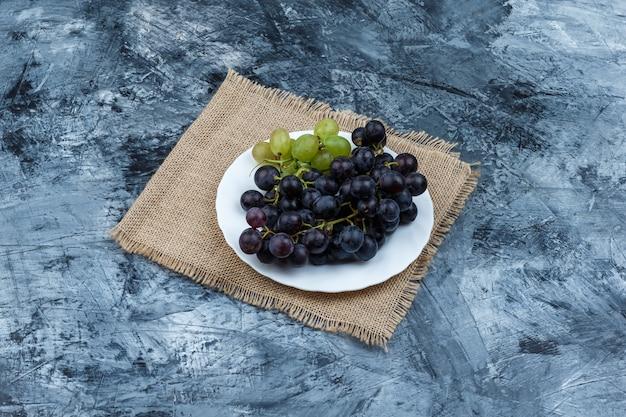 Hoge hoek bekijken witte en zwarte druiven in placemat op donkerblauwe marmeren achtergrond. horizontaal