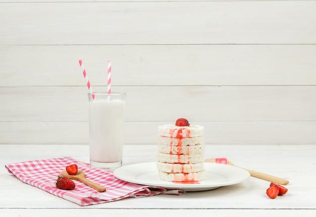 Hoge hoek bekijken witte rijstwafels op plaat met aardbeien, houten lepels en melk op witte houten plank oppervlak.