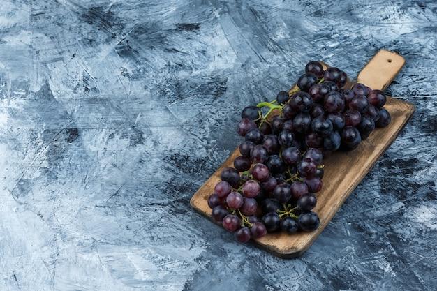 Hoge hoek bekijken zwarte druiven op grungy gips en snijplank achtergrond. horizontaal