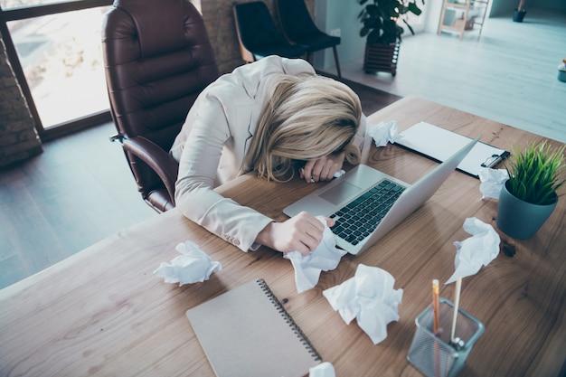 Hoge hoek boven meningsfoto van het hoofd van de zakelijke dame liggend op het bureau moe