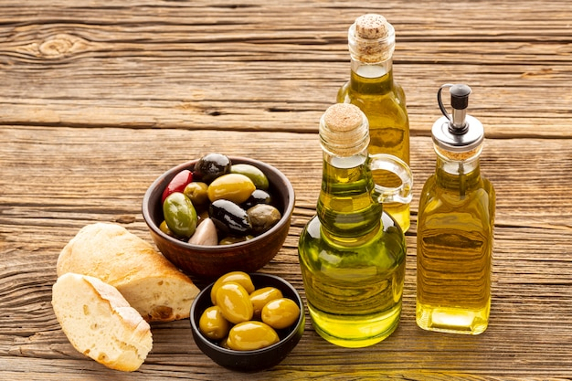 Hoge hoek brood plakjes olijfkommen en olieflessen