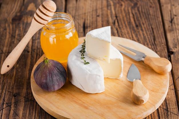 Hoge hoek camembertplak bovenop broodje met honing