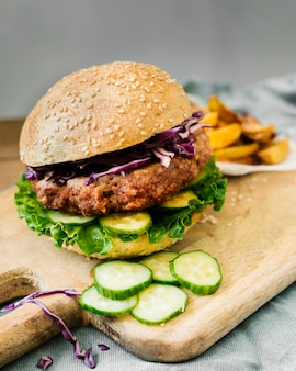 Hoge hoek close-up hamburger met frietjes op een houten bord