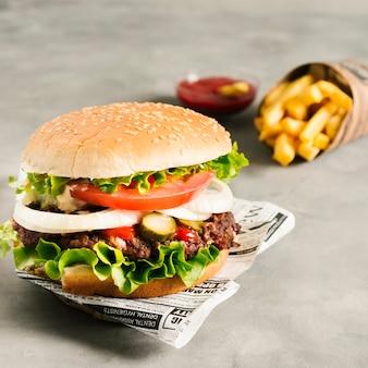 Hoge hoek close-up hamburger met frietjes op krant