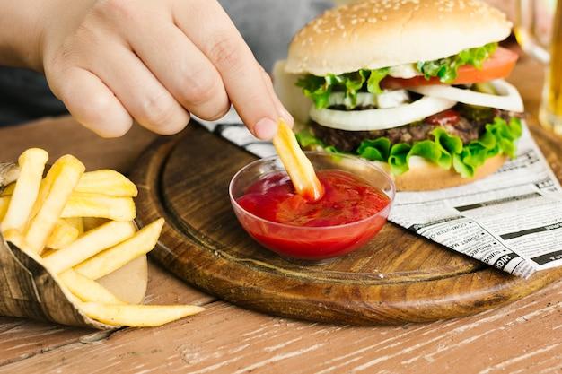 Hoge hoek close-up hand dompelen frietjes met hamburger