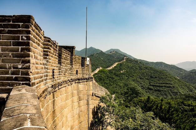 Hoge hoek close-up shot van de beroemde grote muur van china, omringd door groene bomen in de zomer
