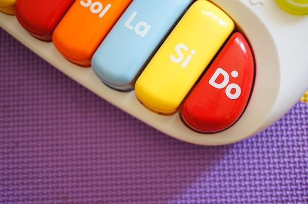 Hoge hoek close-up shot van de kleurrijke toetsen van een stuk speelgoed piano