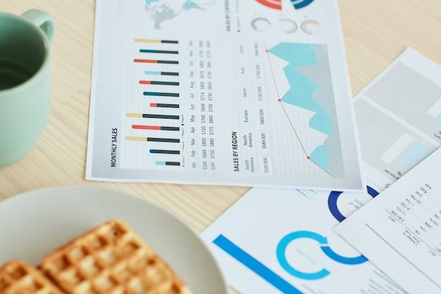 Hoge hoek close-up shot van documenten en ontbijt liggend op de keukentafel