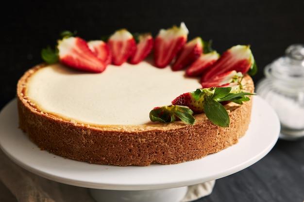 Hoge hoek close-up shot van een strawberry cheesecake op een witte plaat