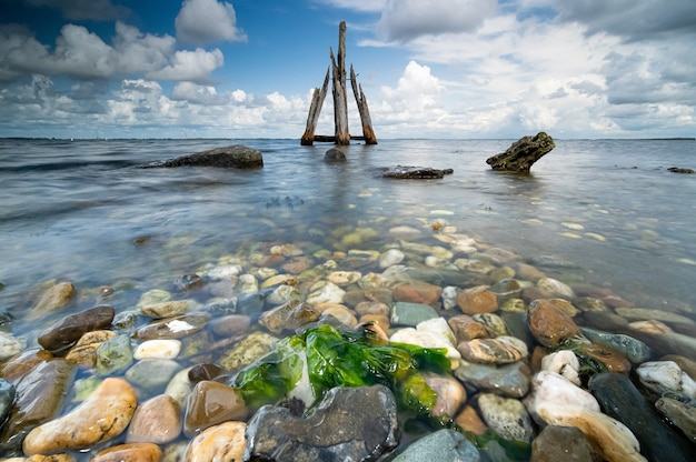 Hoge hoek close-up shot van stenen aan de kust met de kalme zee op de achtergrond