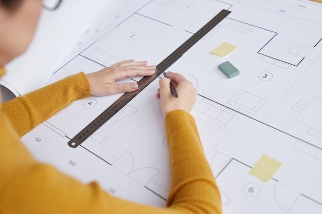 Hoge hoek close-up van vrouwelijke architect tekenen van blauwdrukken en plannen zittend aan een bureau in kantoor,