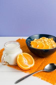 Hoge hoek cornflakes kom met sinaasappel en yoghurt
