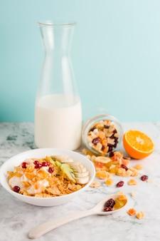 Hoge hoek cornflakes kom met yoghurt en gedroogde vruchten