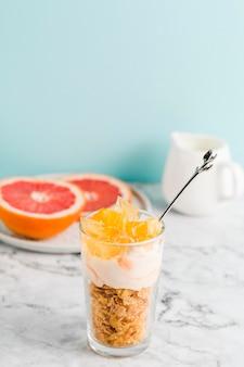 Hoge hoek cornflakes met yoghurt en fruit in glas