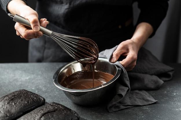 Hoge hoek die van banketbakker chocoladetaart voorbereidt