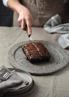 Hoge hoek die van banketbakker in chocoladetaart snijden