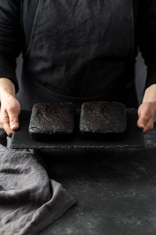 Hoge hoek die van banketbakker twee stukken van cake houdt