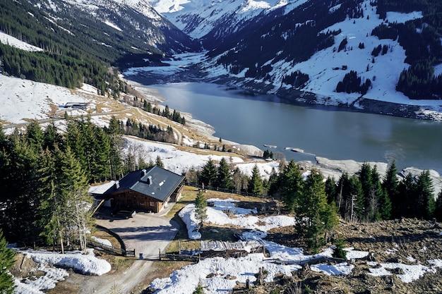 Hoge hoek die van bergen en een rivier met een geïsoleerd huis in het bos op de kust is ontsproten