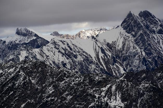 Hoge hoek die van de alpiene bergketen onder de bewolkte hemel is ontsproten