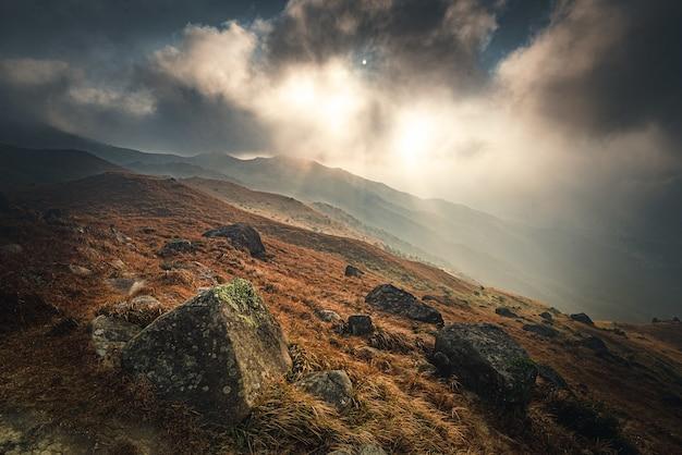 Hoge hoek die van de bemoste stenen in de berg onder de bewolkte zonsonderganghemel is ontsproten