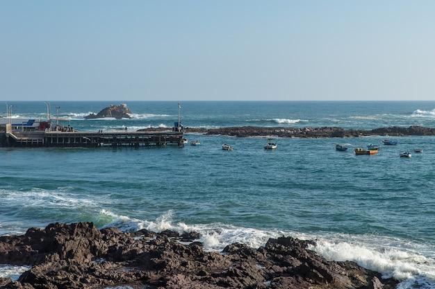 Hoge hoek die van de boten op de zee dichtbij het dok en de rotsachtige kust is ontsproten