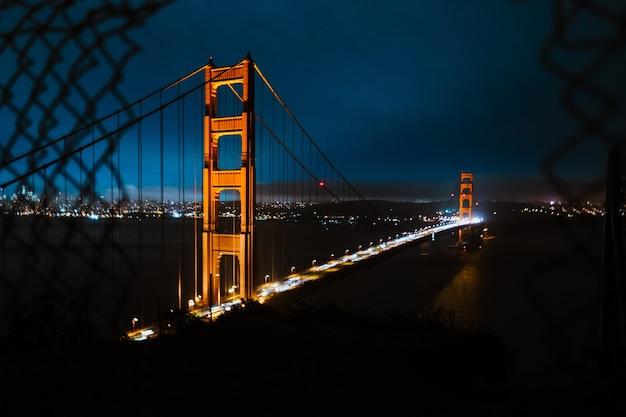 Hoge hoek die van de golden gate bridge onder een donkerblauwe hemel bij nacht is ontsproten
