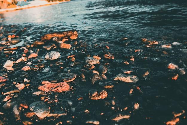 Hoge hoek die van de kleine rotsen en kiezelstenen door een meer is ontsproten dat bij zonsondergang wordt gevangen