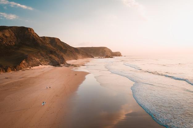 Hoge hoek die van de oceaangolven is ontsproten die naar het strand naast rotswanden onder de heldere hemel komen