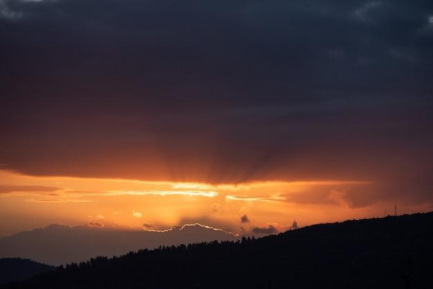 Hoge hoek die van de zonsondergang in de donkere hemel over de bergen is ontsproten