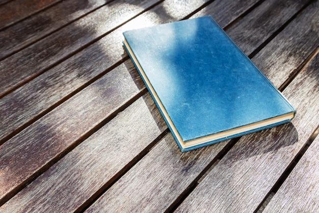 Hoge hoek die van een blauw boek op een houten oppervlakte is ontsproten