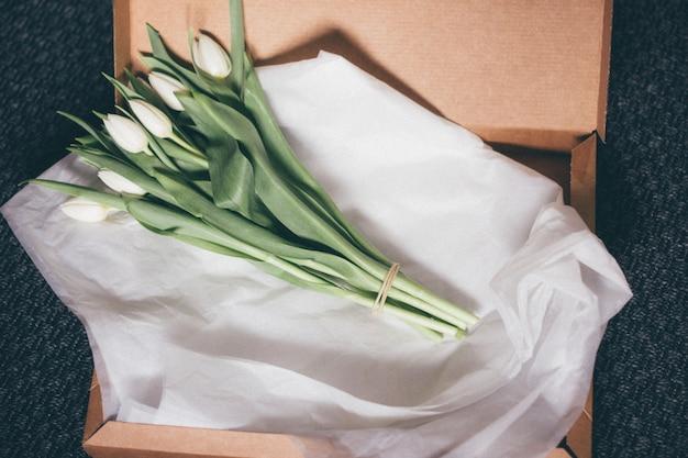 Hoge hoek die van een boeket van mooie witte tulpen op een witboek is ontsproten