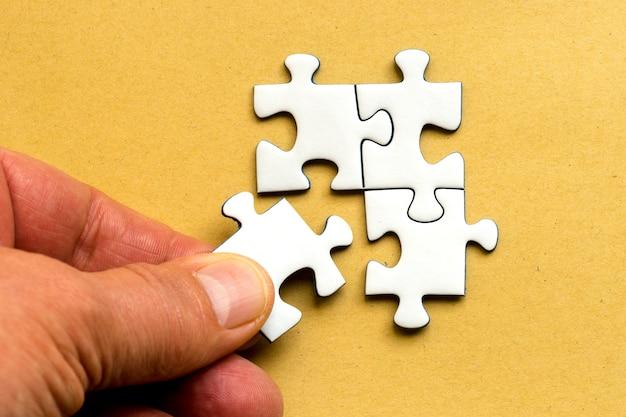 Hoge hoek die van een menselijke hand is ontsproten die een stuk van de puzzel aan de rest bevestigt