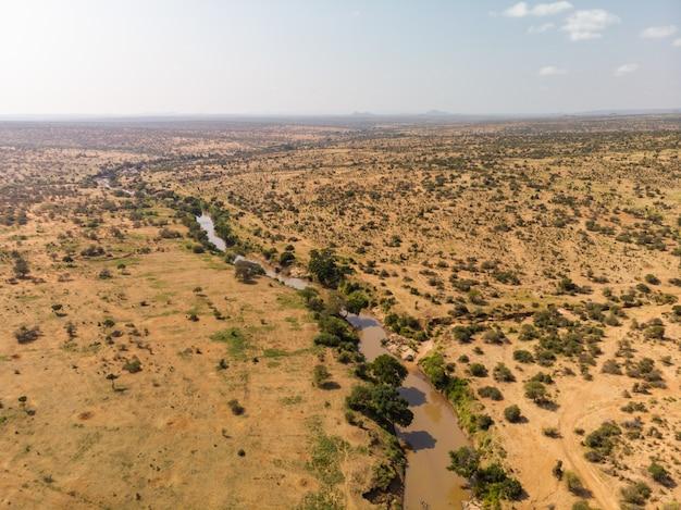 Hoge hoek die van een modderige rivier is ontsproten die door de woestijn gaat die in samburu, kenia wordt gevangen