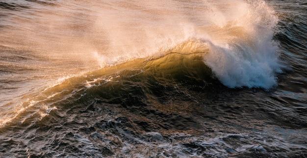 Hoge hoek die van een mooie grote golf in de oceaan met een landschap van zonsondergang is ontsproten