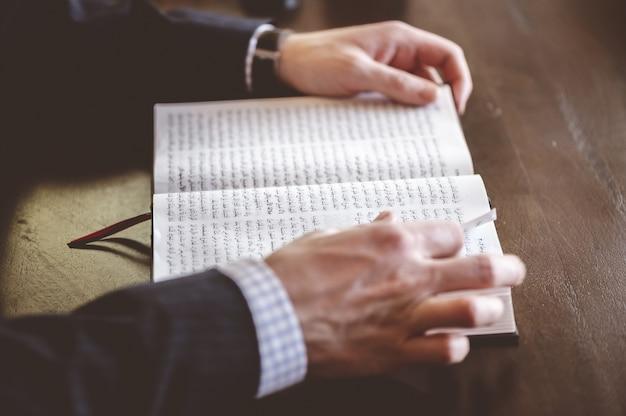 Hoge hoek die van een persoon is ontsproten die een arabisch boek leest