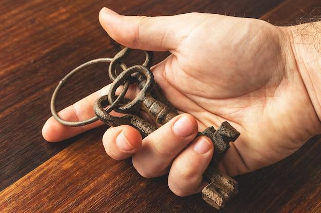 Hoge hoek die van een persoon is ontsproten die enkele oude en verroeste sleutels over een houten oppervlakte houdt