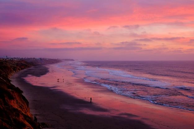 Hoge hoek die van een prachtig strand onder de adembenemende zonsonderganghemel is ontsproten