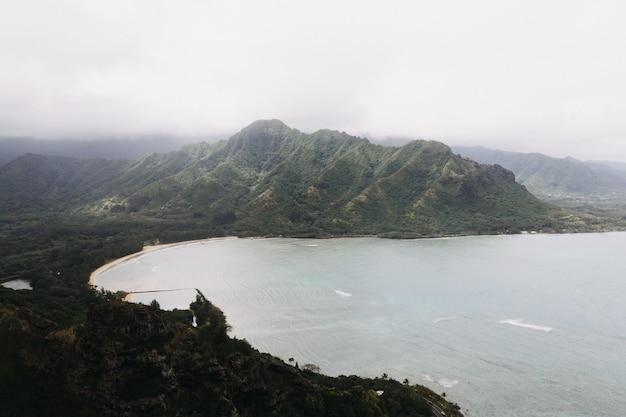 Hoge hoek die van een prachtige kust met een witte bewolkte hemel is ontsproten