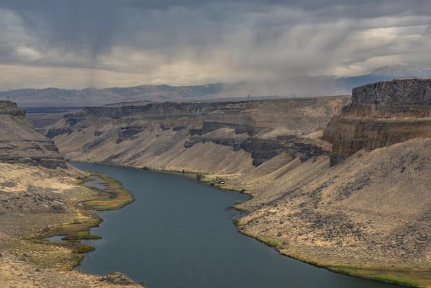 Hoge hoek die van een rivier in het midden van klippen met bergen en een bewolkte hemel is ontsproten
