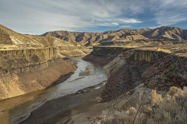Hoge hoek die van een rivier in het midden van klippen met bergen in de verte onder een blauwe hemel is ontsproten