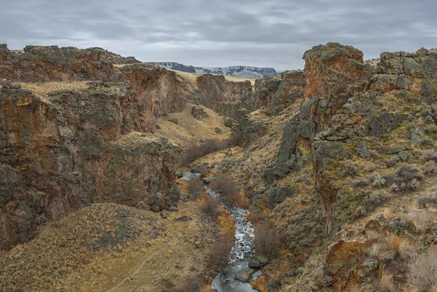 Hoge hoek die van een rivier in het midden van woestijnbergen is ontsproten met een bewolkte hemel