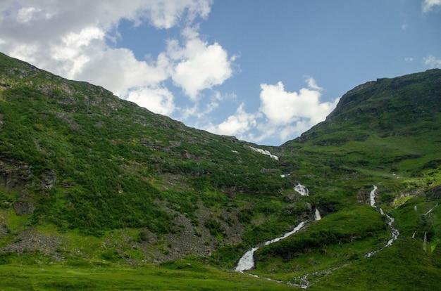 Hoge hoek die van een smalle sloot in de hoge groene bergen in noorwegen is ontsproten