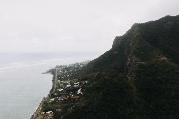 Hoge hoek die van een steile berg in de kust met een bewolkte hemel is ontsproten