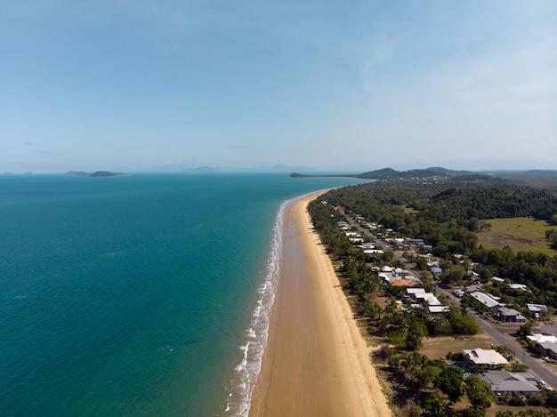 Hoge hoek die van een strand met een kleine stad aan de kust is ontsproten