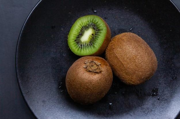 Hoge hoek die van een verse kiwi in een zwarte plaat is ontsproten