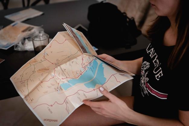 Hoge hoek die van een vrouw is ontsproten die een kaart vasthoudt en leest om haar weg te vinden