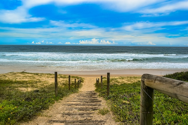 Hoge hoek die van een weg met houten leuningen is ontsproten die naar de zee leidt