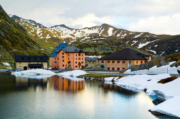 Hoge hoek die van enkele huizen bij een meer dichtbij de met sneeuw bedekte bergen is ontsproten